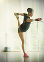 Woman holding king dancer pose in gym studio - CAIF11786