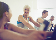 Smiling women talking on exercise bikes at gym - CAIF11789