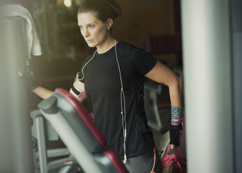 Focused woman stretching leg at gym - CAIF11792