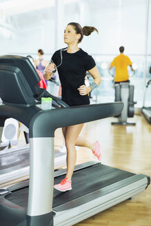Woman running on treadmill with headphones at gym - CAIF11795