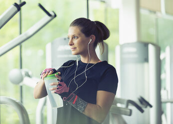 Woman with headphones resting and drinking water at gym - CAIF11798