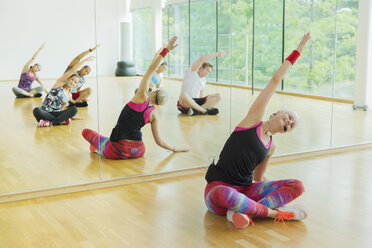 Fitness instructor leading class stretching arms - CAIF11804