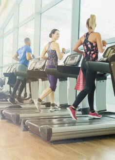 Man and women jogging on treadmills at gym - CAIF11807