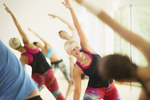 Smiling fitness instructor leading aerobics class stretching arms - CAIF11816