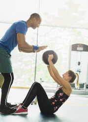 Personal trainer guiding woman with medicine ball at gym - CAIF11819