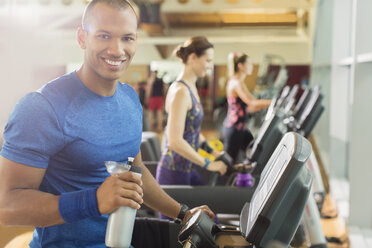 Portrait smiling man with water bottle on treadmill at gym - CAIF11822