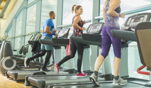 Man and women running on treadmills at gym - CAIF11831