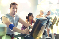 Portrait smiling man riding exercise bike at gym - CAIF11834