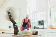 Personal trainer guiding woman with fitness ball between legs - CAIF11837