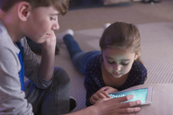 Brother and sister playing game on digital tablet - CAIF11849