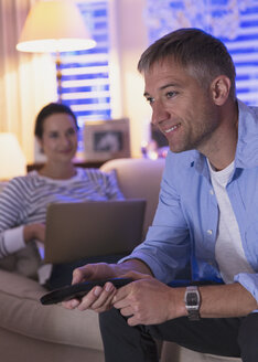 Wife with laptop and husband watching TV in living room - CAIF11858