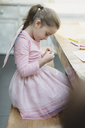 Girl in fairy wings coloring at dining table - CAIF11873
