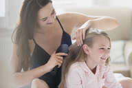 Mother brushing daughter's hair - CAIF11900