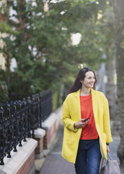 Smiling woman walking with cell phone in urban park - CAIF11903