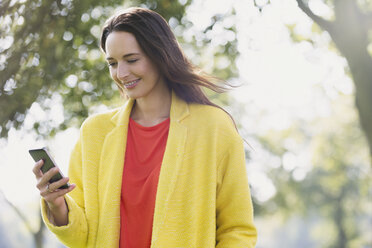 Smiling woman using cell phone in park - CAIF11906