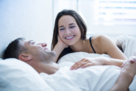 Smiling couple laying in bed talking - CAIF11912