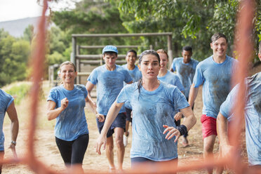 Team running in rain on boot camp obstacle course - CAIF11933