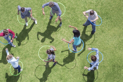 People spinning in plastic hoops in sunny grass - CAIF11936