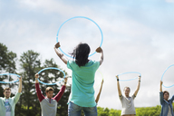 Team holding plastic hoops overhead - CAIF11960