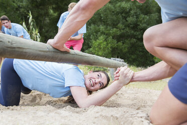 Teammate helping woman under log on boot camp obstacle course - CAIF11978