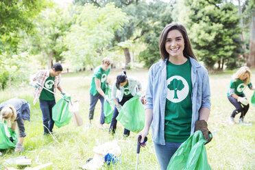 Portrait of smiling environmentalist volunteer picking up trash - CAIF11990