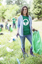 Portrait of smiling environmentalist volunteer picking up trash - CAIF11993
