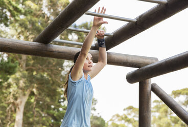 Determined woman crossing monkey bars on boot camp obstacle course - CAIF11999