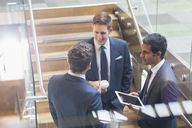 Businessmen with digital tablet and coffee talking on stairs - CAIF12056