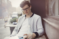 Young man with eyeglasses and headphones using digital tablet at sidewalk cafe - CAIF12089