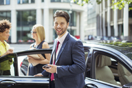 Businessman smiling outside car - CAIF12098