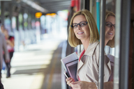 Businesswoman smiling in train doorway - CAIF12101