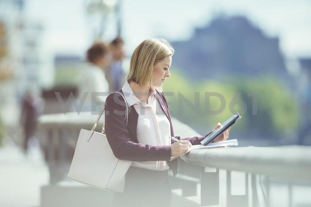 Businesswoman using digital tablet at urban waterfront - CAIF12104 - Paul Bradbury/Westend61