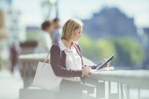 Businesswoman using digital tablet at urban waterfront - CAIF12104
