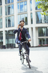 Businessman talking on cell phone on bicycle - CAIF12122