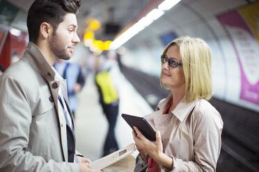 Business people talking in subway station - CAIF12128