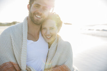 Portrait of young couple standing on beach - CAIF12131