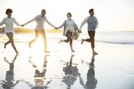 Group of four friends holding hands and running on beach - CAIF12134
