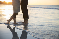 Legs of young couple standing on beach - CAIF12137