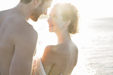 Portrait of smiling young couple in sunlight - CAIF12158