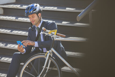 Businessman in suit with bicycle and helmet texting with cell phone on stairs - CAIF12167