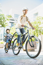 Mother and son riding bicycles on urban path - CAIF12173