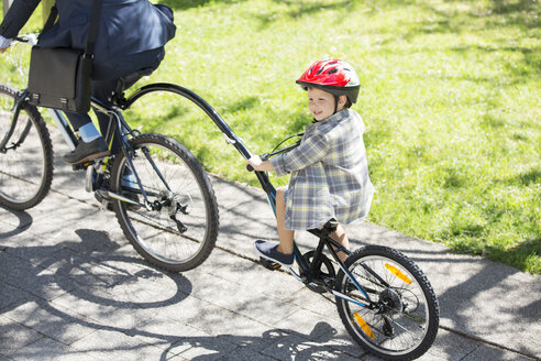 Boy riding tandem bicycle with businessman father in sunny park - CAIF12176