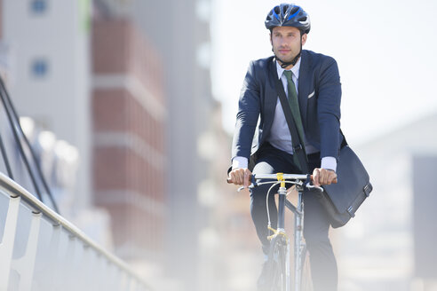 Businessman in suit and helmet riding bicycle in city - CAIF12182