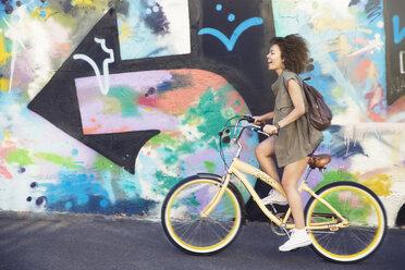 Woman riding bicycle along urban multicolor graffiti wall - CAIF12185