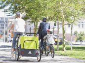 Families riding bicycles in sunny urban park - CAIF12191