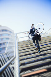 Businessman carrying bicycle up urban stairs under sunny blue sky - CAIF12194