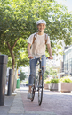 Young woman with helmet riding bicycle in urban park - CAIF12197