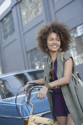 Smiling young woman with afro holding bicycle on urban street - CAIF12200