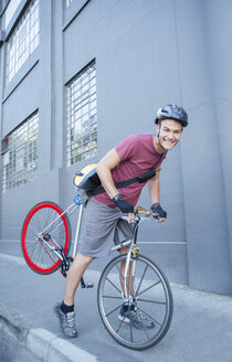Portrait smiling bicycle messenger with helmet leaning forward on urban sidewalk - CAIF12203