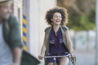 Enthusiastic woman with afro riding bicycle - CAIF12206